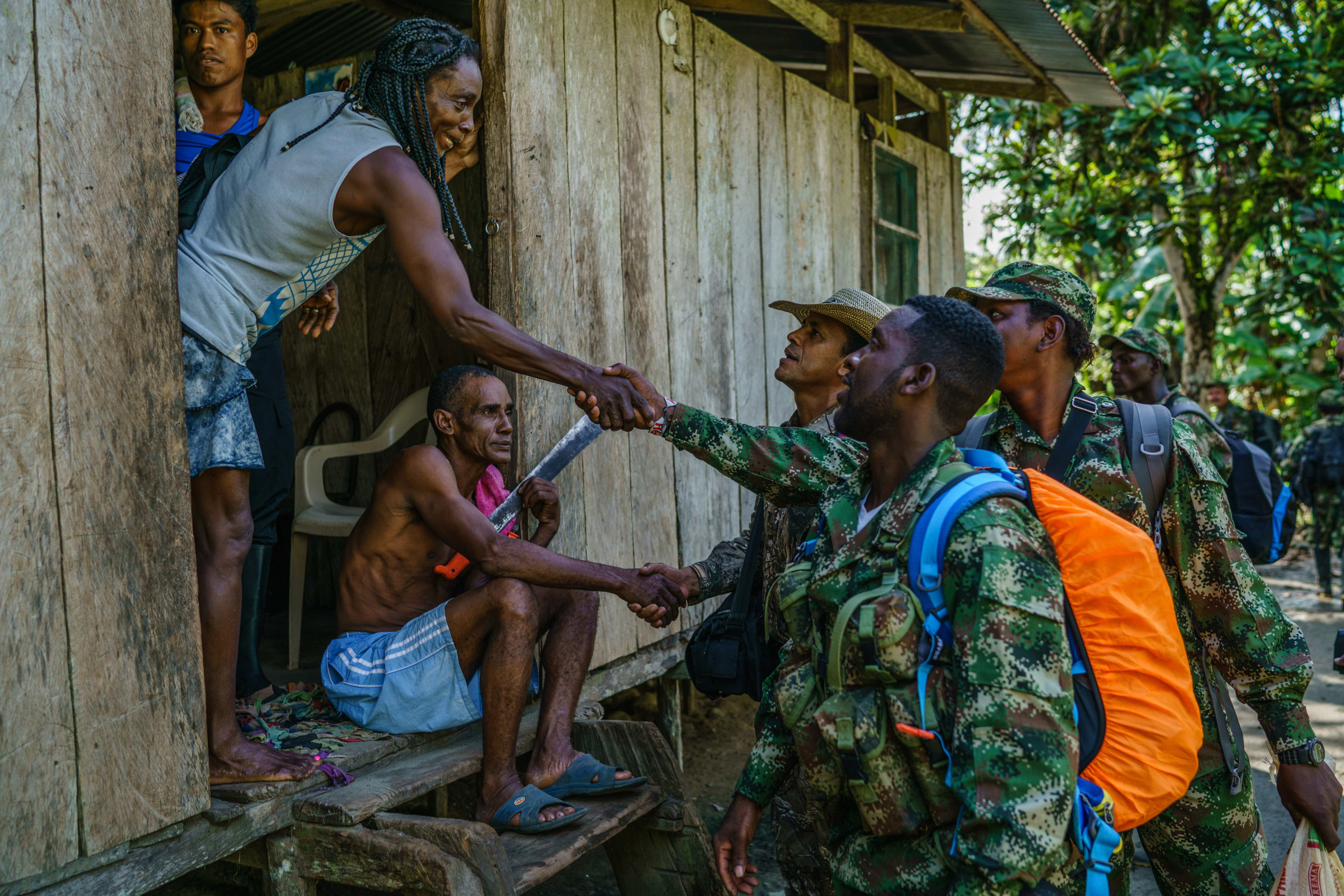 FARC members shake hands with villagers in rural Colombia. © Federico Rios