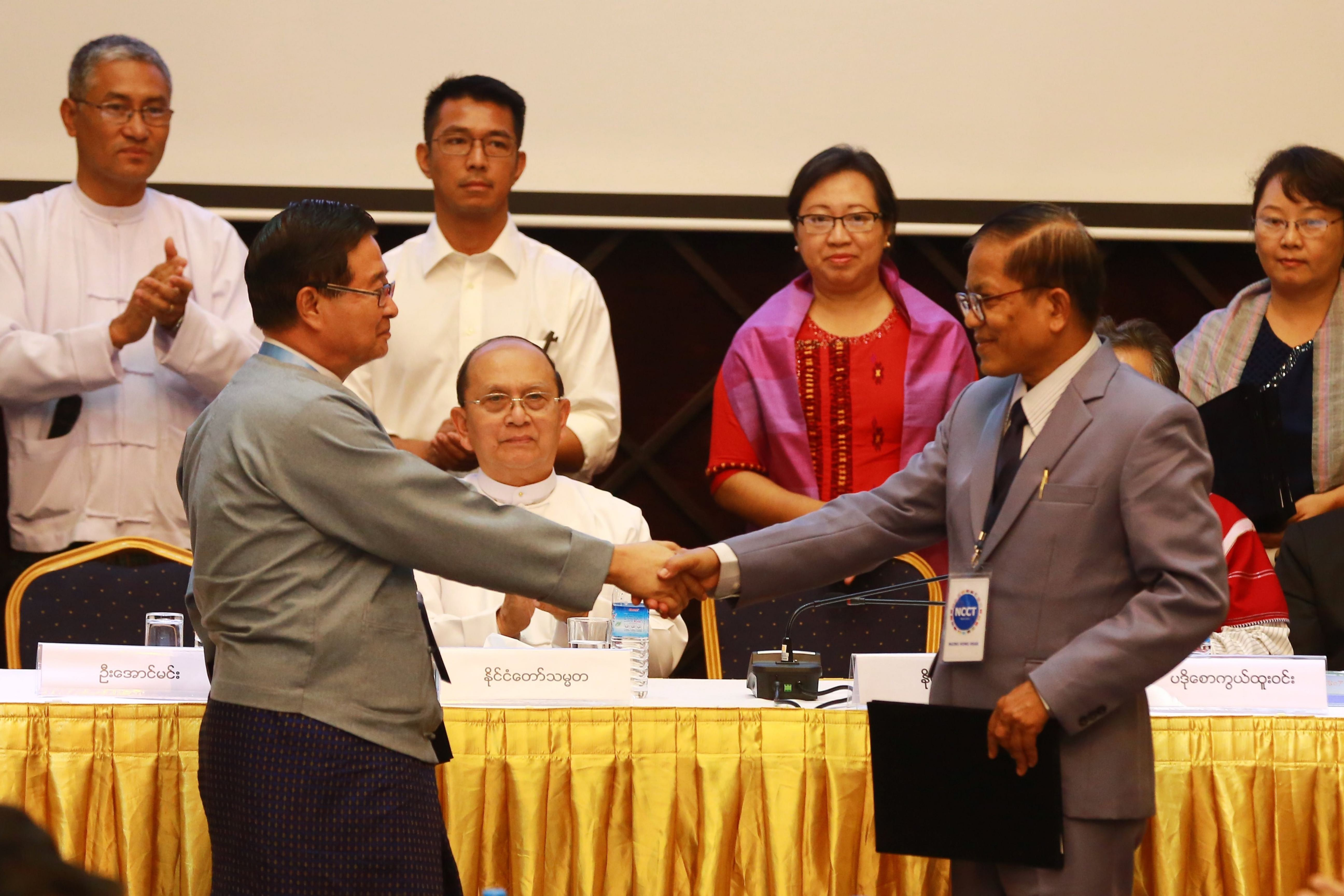 Myanmar President Thein Sein (seated, centre) looks on as Aung Min (left), vice chairperson of the Union Peace Working Committee, shakes hands with Naing Han Tha (right), a leader of the Nationwide Ceasefire Coordinating Team, after they sign a nationwide ceasefire draft agreement at the Myanmar Peace Centre in Yangon on 31 March 2015. Ja Nan Lahtaw is pictured (standing, centre). © STR/AFP via Getty Images