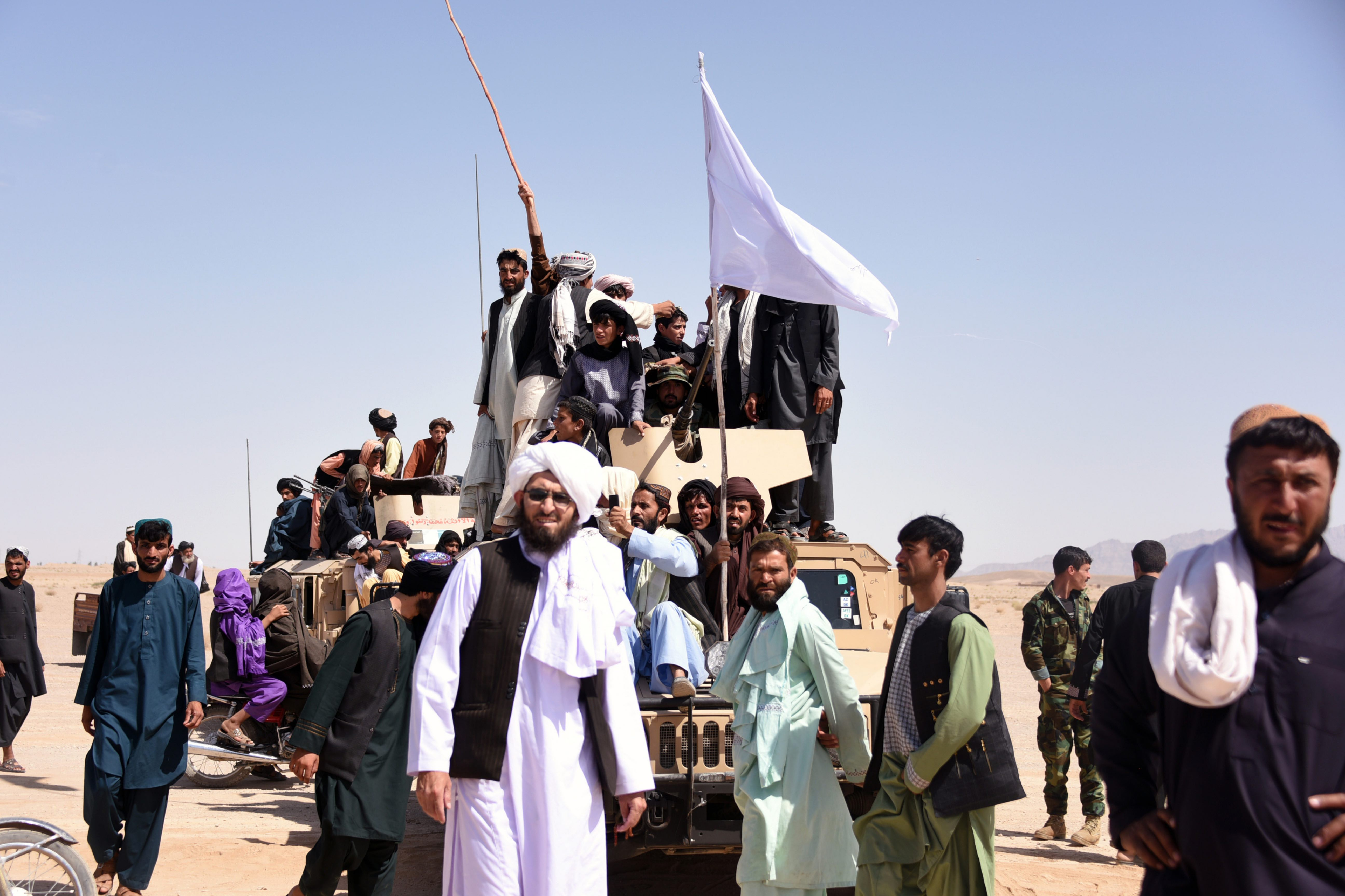 Taliban members and local residents stand on an armoured Humvee vehicle of the Afghan National Army (ANA) as they celebrate ceasefire together on the third day of Eid in Maiwand district of Kandahar province, June 2018. © Javed Tanveer/AFP via Getty Images