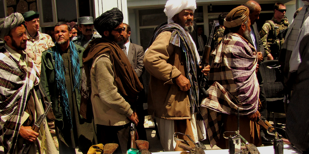Former Taliban fighters line up to hand over their rifles to the Government of the Islamic Republic of Afghanistan