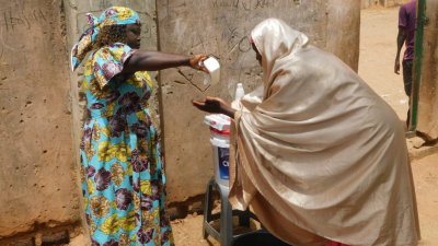 Women sanitise their hands in Nigeria