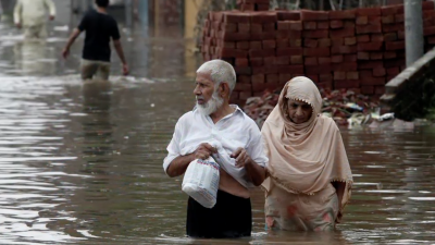 Two people walking through floods in Jammu and Kashmir