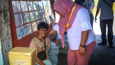 Norhanie Taha Mamasabulod in Layog's Community Safety Working Group, talks with a street vendor with disabilities about local security issues.