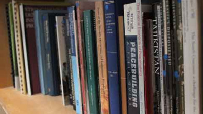 a row of peacebuilding books lined up on a shelf, spines showing