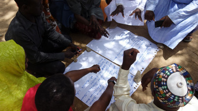 Workshop participants gathered around paper in northeast Nigeria