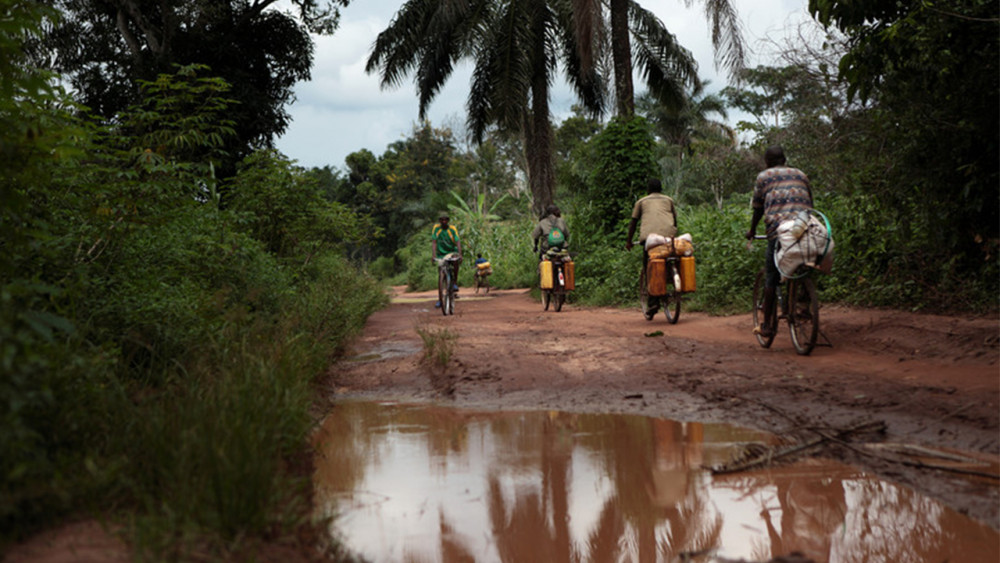 Young men cycle on the road between South Sudan and DRC