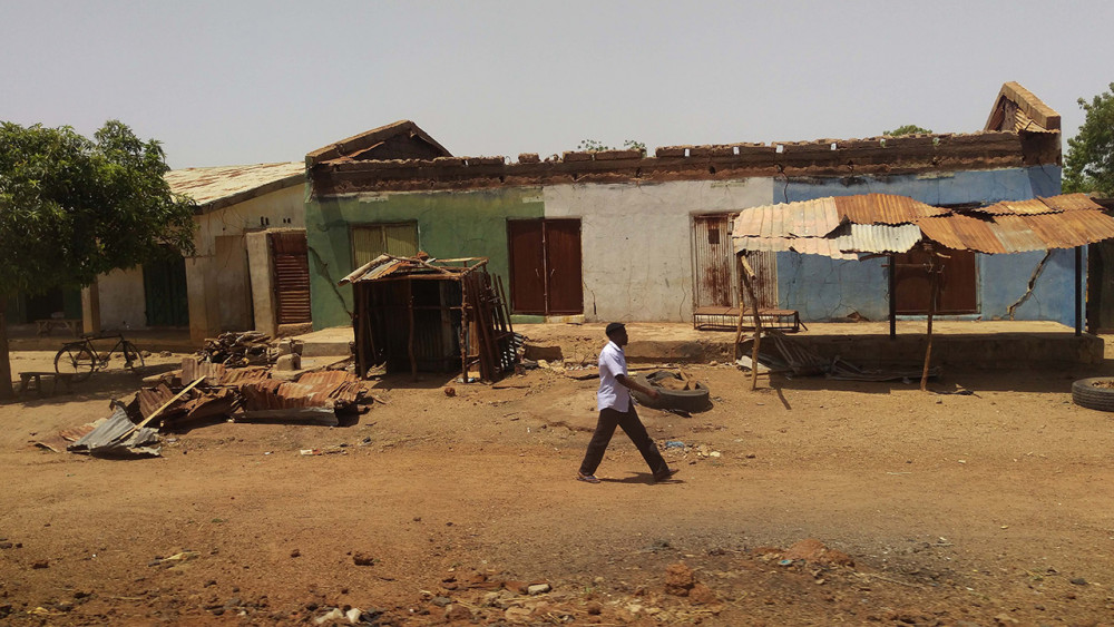 Young man walking past buildings in northeast Nigeria