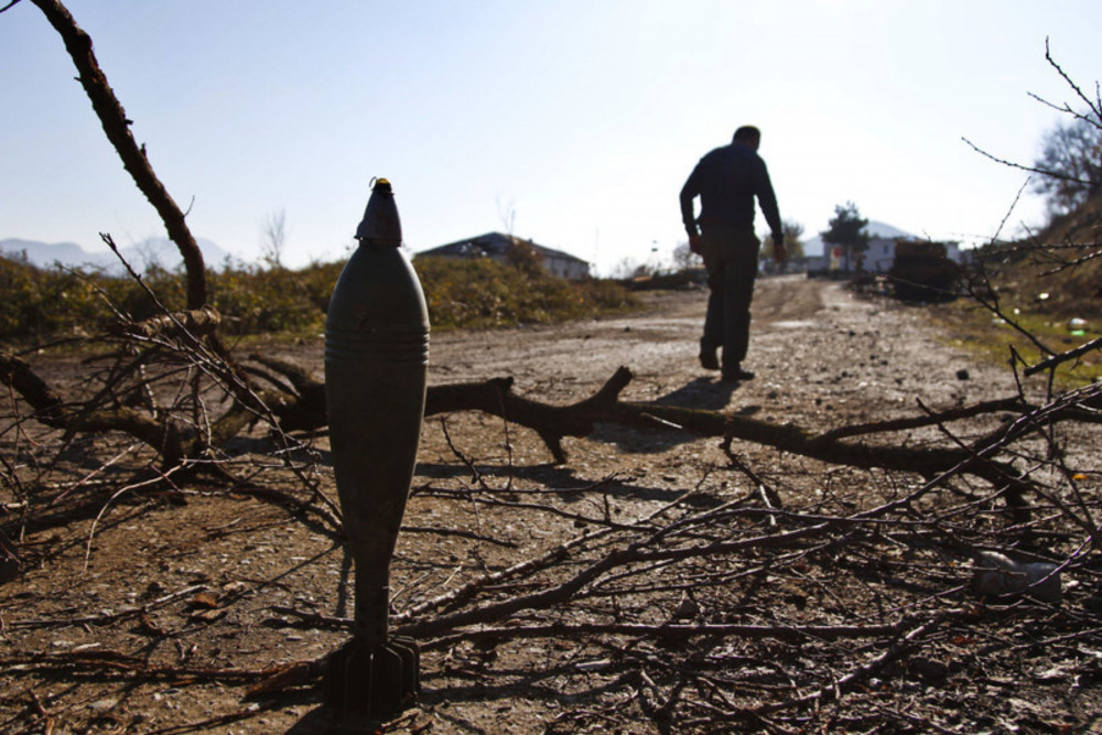 An unexploded mortar round is stood on its tail outside the destroyed wreckage of a munitions warehouse in the village of Aygestan near Stepanakert, Nagorny Karabakh