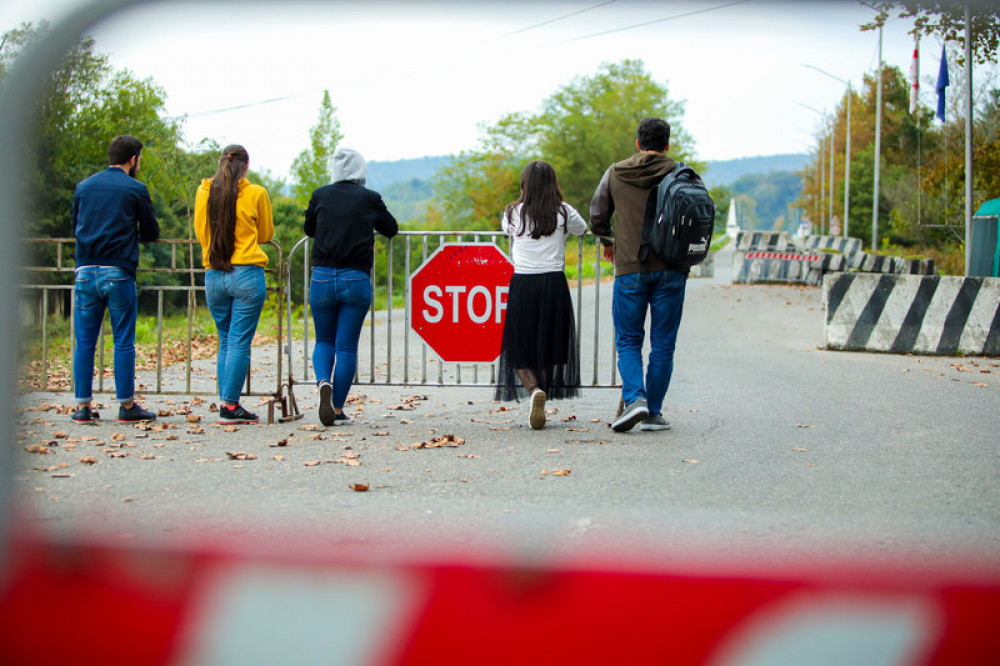 Young people standing at road block