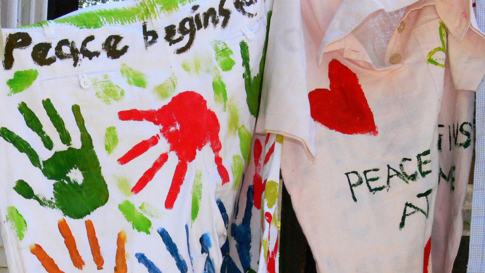 clothes hung up, with handprints and messages of peace on them.
